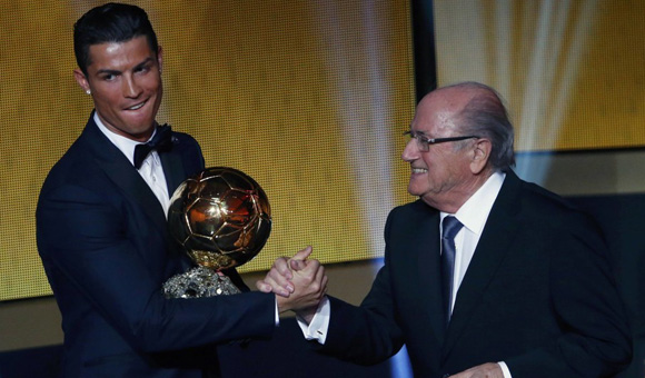 Real Madrid and Portugal forward Ronaldo reacts as he receives the FIFA Ballon d'Or award from FIFA President Blatter during the FIFA Ballon d'Or 2014 soccer awards ceremony in Zurich